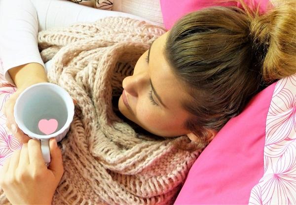 Vrouw neemt kopje thee tegen griep
