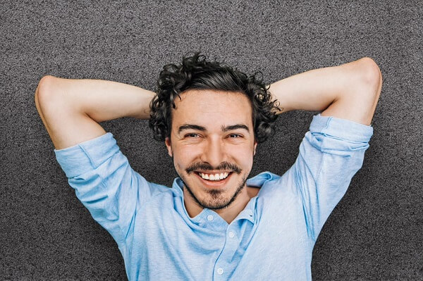 Een man ligt glimlachend op een schoonloopmat met handen onder zijn hoofd