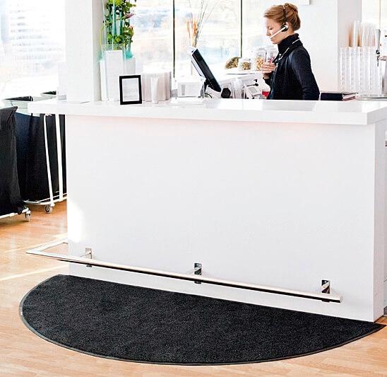 Een halfronde mat liggend voor een balie