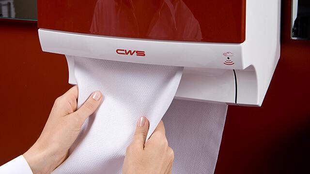 Handdoekdispenser waar iemand een stuk katoen pakt