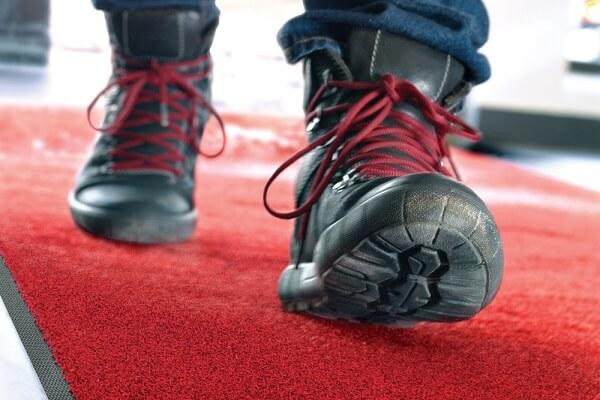 Met werkschoenen lopen over schoonloopmat