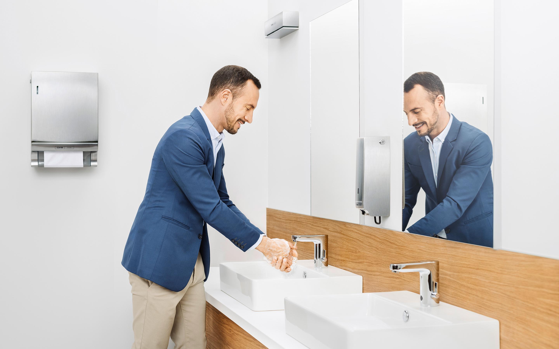 Ein Mann wäscht sich die Hände in einem mit CWS Produkten ausgestatteten Bad.