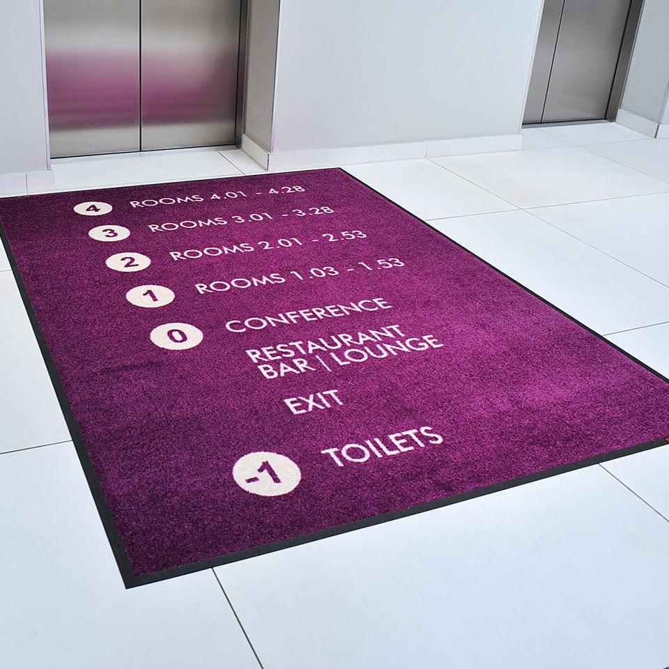 Eine Logomatte im Eingangsbereich zum Fahrstuhl