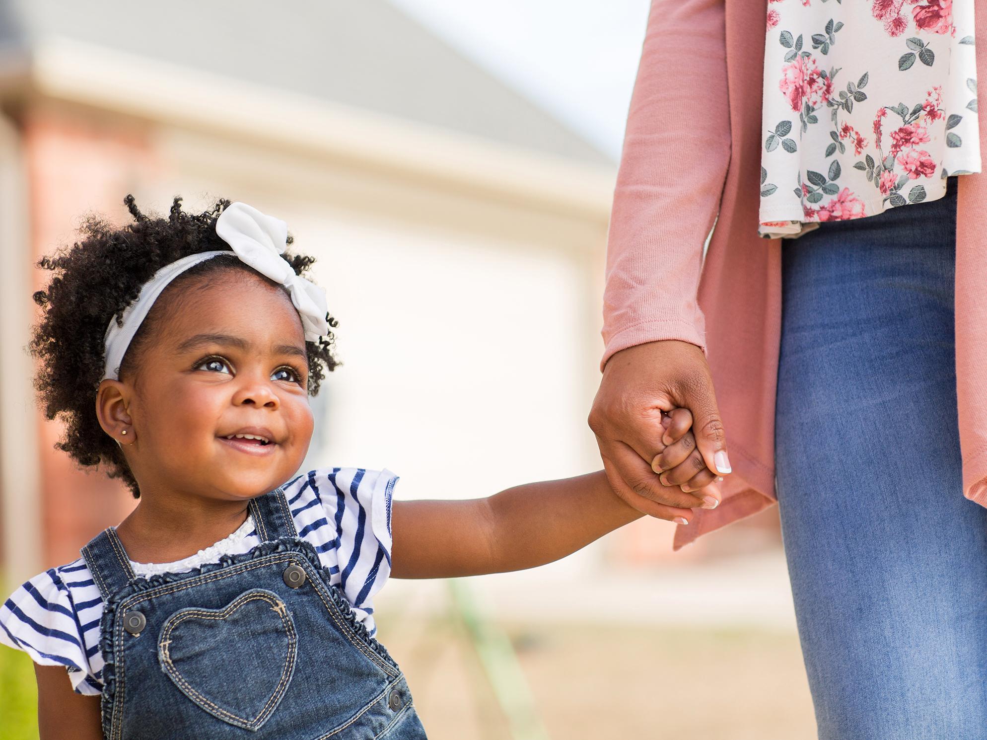 Verantwortung: Erwachsene Frau hält die Hand eines Kindes