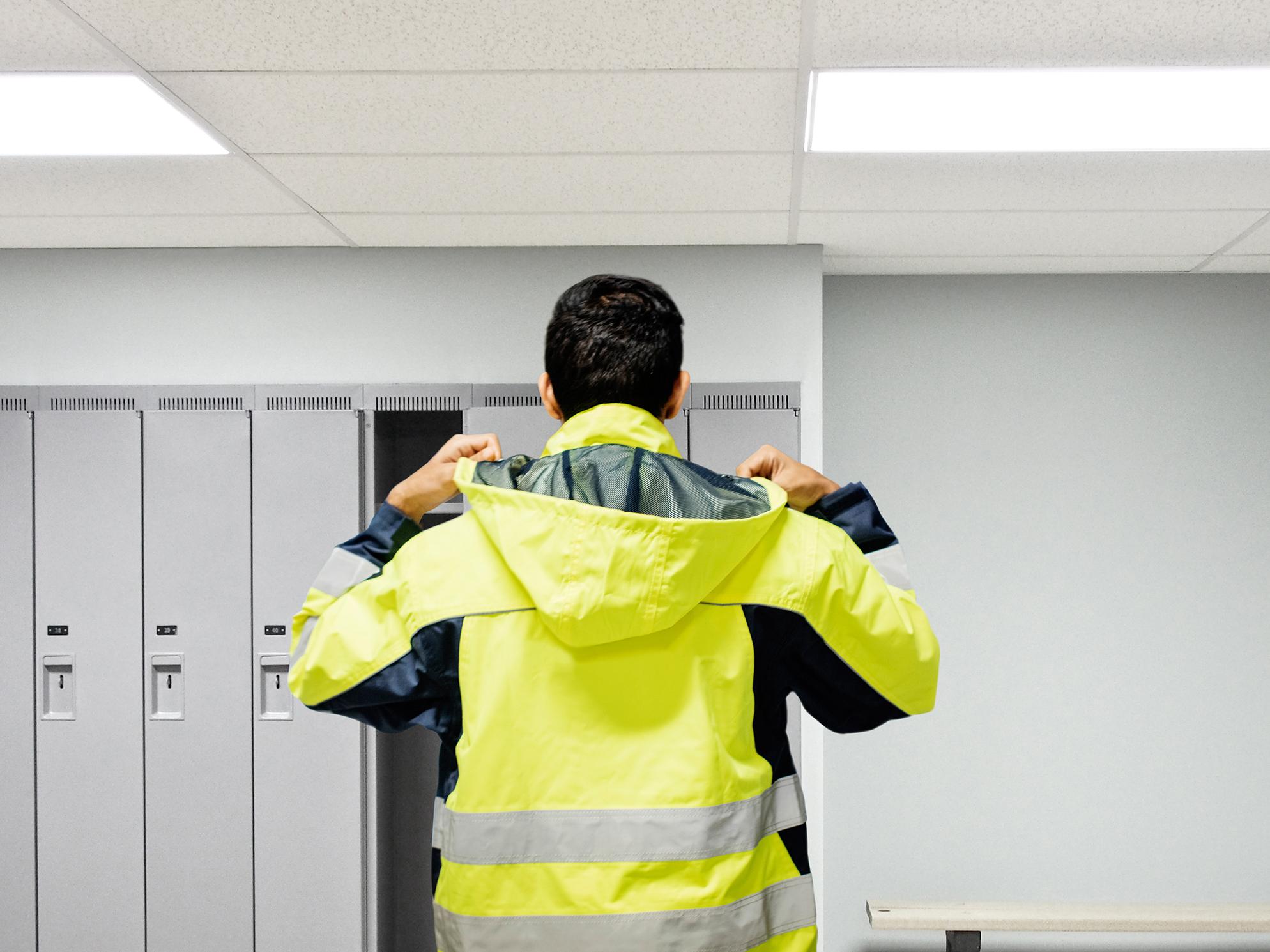 Ein Mann mit gelber Warnjacke steht vor einem Spind im Umkleideraum.