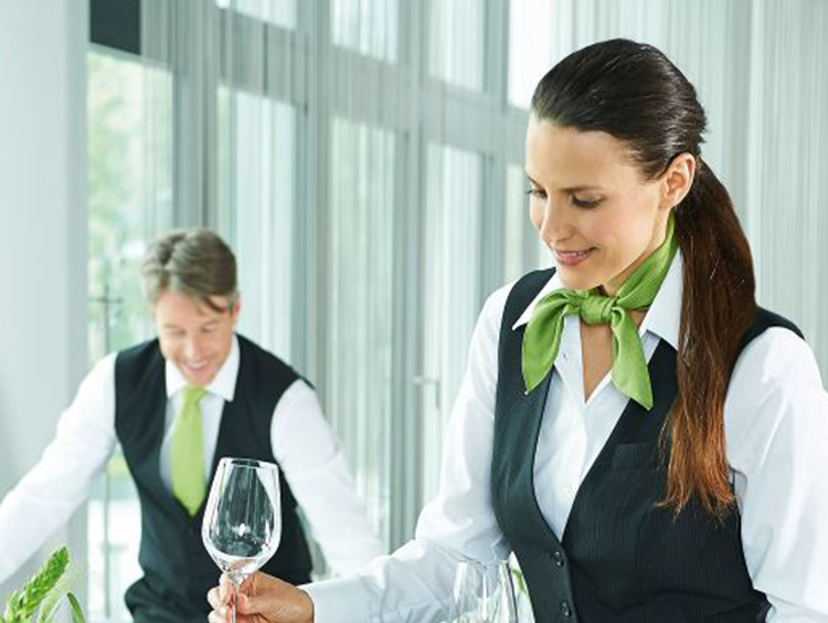 Hotelpersonal mit einheitlicher Kleidung  decken Tisch im Restaurant