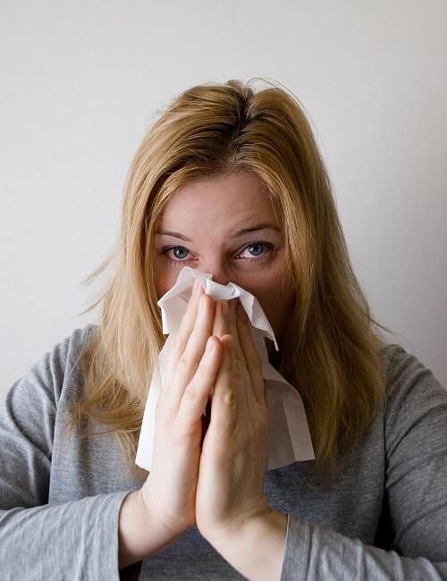 Verkouden vrouw met griep snuit haar neus